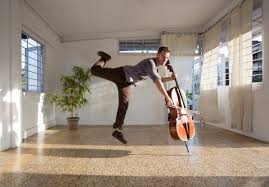 man leaping behind cello